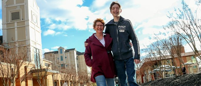 A smiling mother and son walk past the UA Little Rock residence halls.