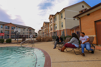 Three students relax at the pool at the University Village.
