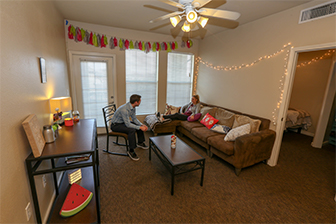 Two students hang out in the living room of an apartment at the University Village.