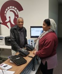Man and woman receive in-person training on VoIP equipment.