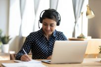 Seated female student wearing headset, studying online with laptop