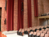Photo of the Stella Boyle Concert Hall looking out from the stage to the auditorium. There is a tall brick wall with long hanging drapes on the side of the seating area where there are rows of cushioned seats, The hall is empty of people.