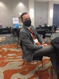 Photo of UALR CIO Thomas Bunton sitting at a table during the 2021 Ark. IT Symposium.