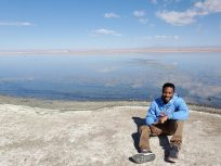 Photo of a male Study Abroad student sitting on a rock - behind is a panoramic view of mountains likely n a foreign country.