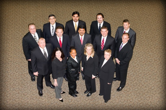 Group of 14 Weekend MBA students, all dressed in black suits.