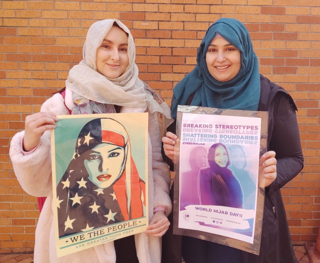 """Two female students wearing the hijab traditional head covering hold World Hijab Day posters that read """"We The People Are Greater Than Fear"""" and """"Shattering Stereotypes, #FreeInHijab, World Hijab Day""""."""