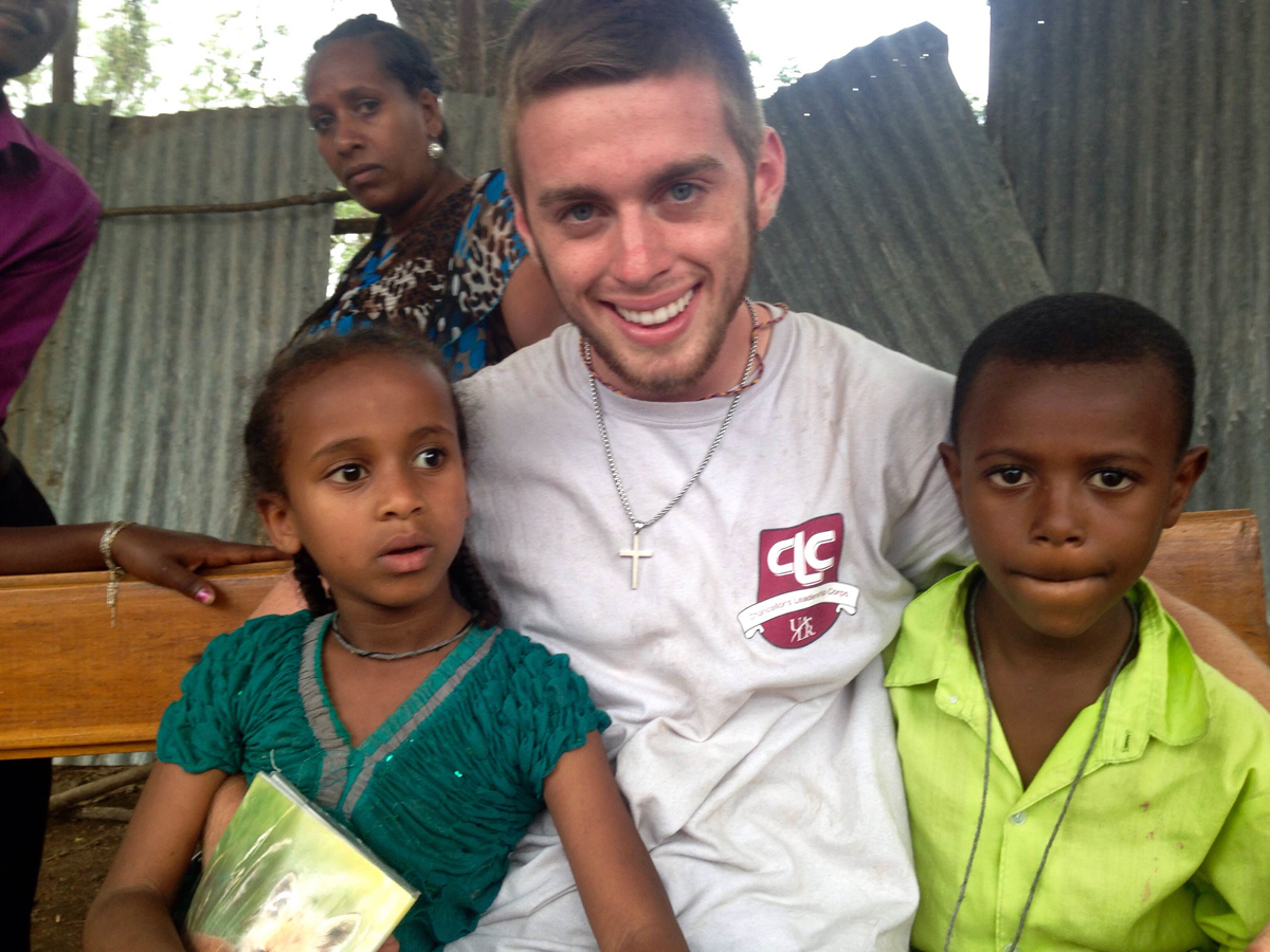 James Sellers poses with two children he met during a missions trip