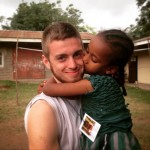 A young child gives James Sellers a kiss on the cheek during his missions trip
