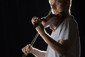 UALR student and traditional-style fiddler Everett Elam photographed while playing the fiddle