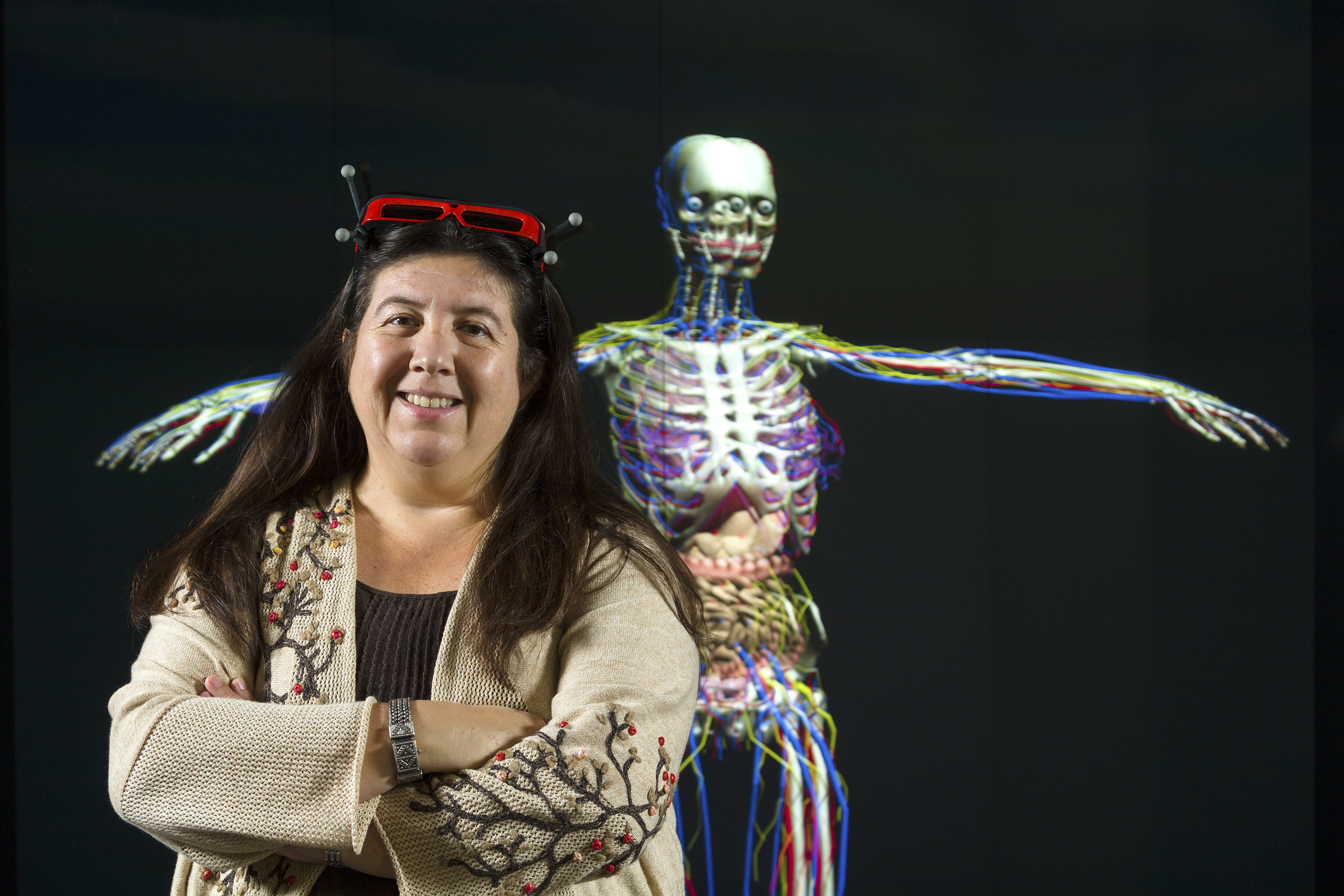 Dr. Carolina Cruz-Neira with a virtual human skeleton in the background