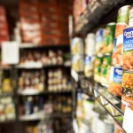 A photograph of metal shelves filled with canned food in the UALR Trojan Food Pantry