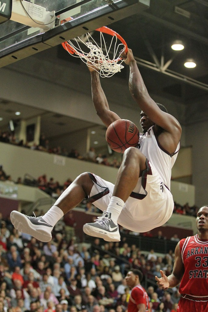 Little Rock Trojans player Roger Woods holds the rim after a slam dunk