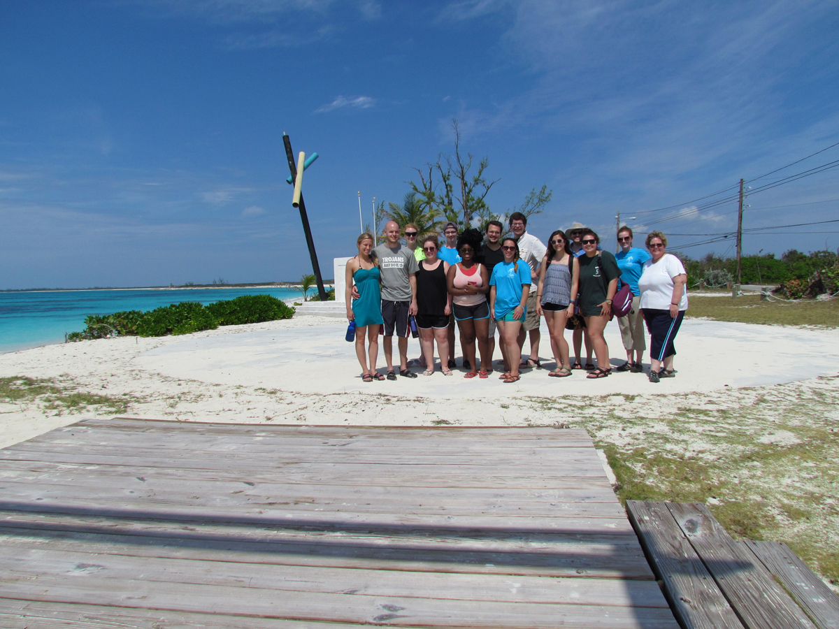 A group shot of the students next to the ocean.