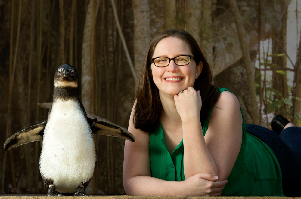 Jessica Erwin poses with a penguin at Little Rock's zoo. Photo by Lonnie Timmons III