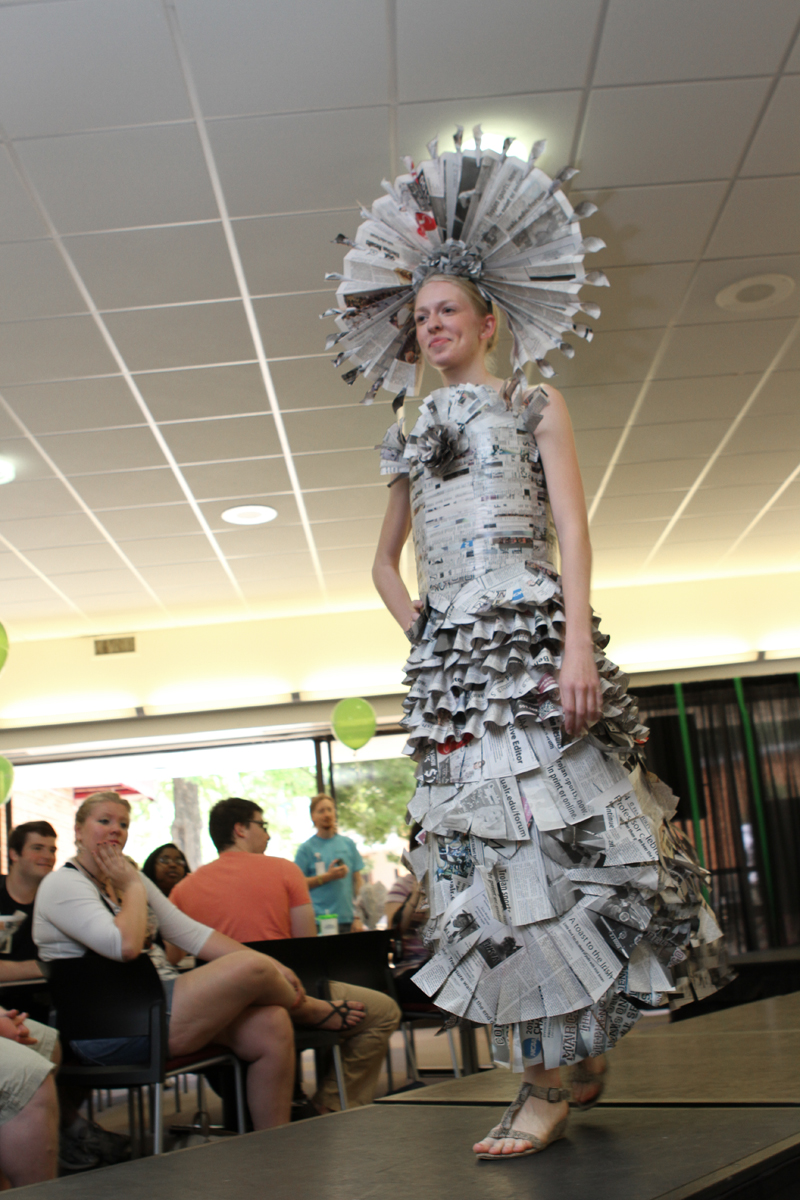 Student poses on catwalk, showing off her newspaper dress.