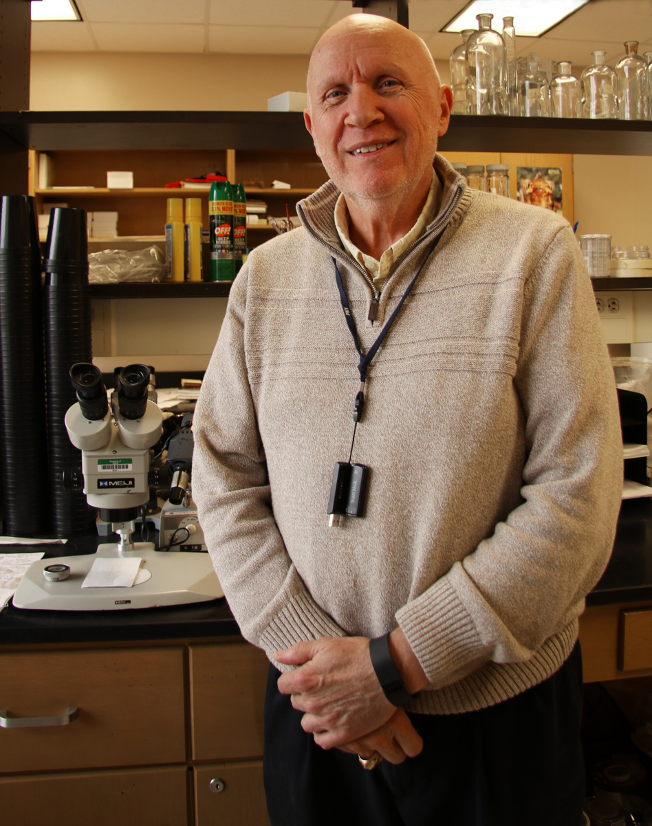 Dr. Carl Stapleton stands in front of the lab equipment used to test mosquitos.
