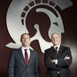 UALR's Chasse Conque and Christian O'Neal pose in front of a large Trojan logo