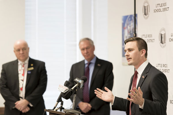 Little Rock School District Superintendent Michael Poore, left, and University of Arkansas at Little Rock Chancellor Andrew Rogerson listen as UALR Student Government Association President Connor Donovan relates his student experience during an announcement of Trojan Pathway, a new partnership to benefit Little Rock high school students.