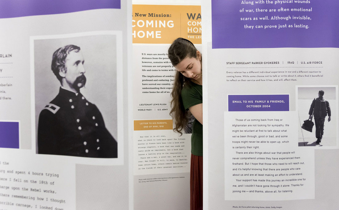 Chelsea Young setups the War Comes Home exhibit at the Ottenheimer Library .