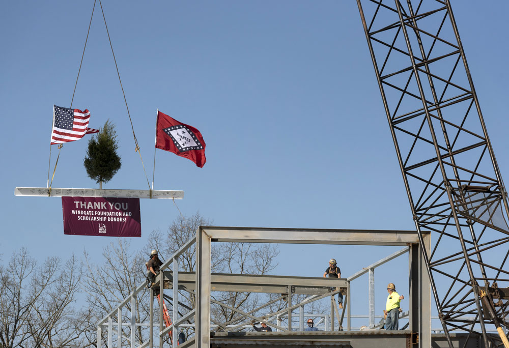 Nabholz construction officials raise a 400-pound beam to the top floor of the Windgate Center on Feb. 23. Photo by Lonnie Timmons III/UA Little Rock Communications.