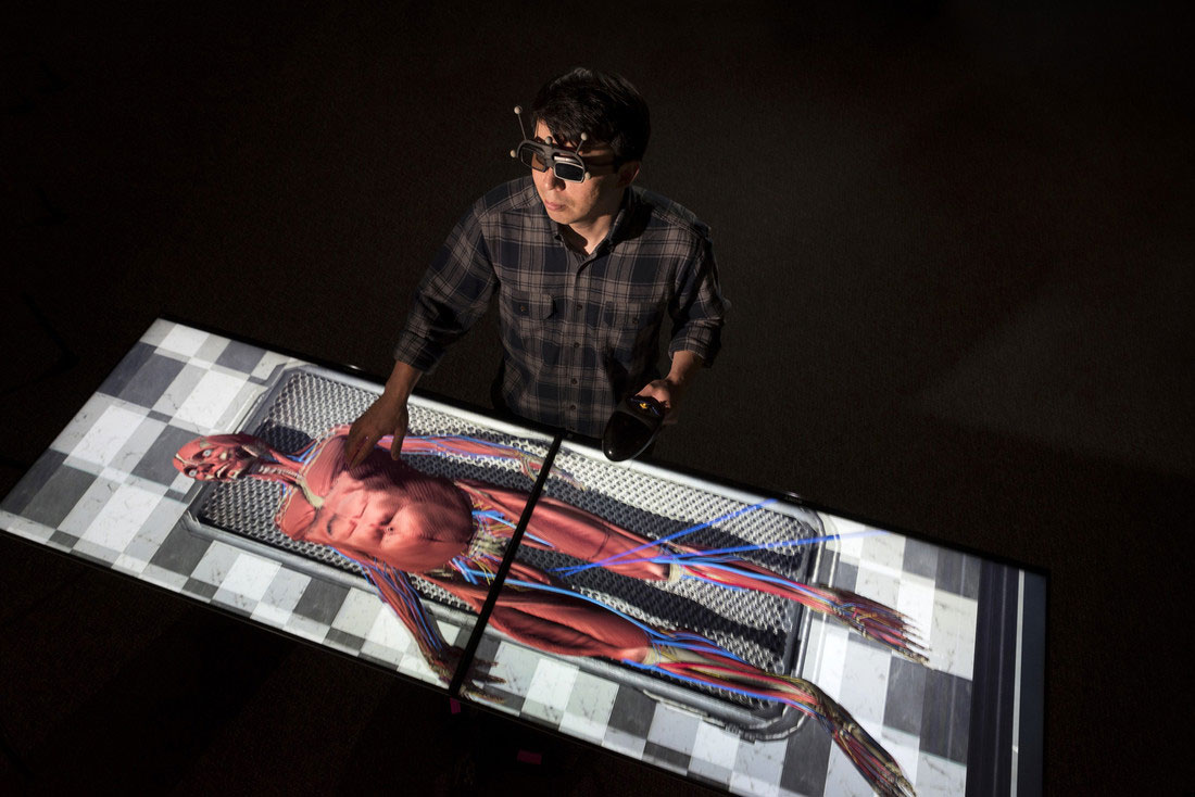 Emerging Analytics Center Student Researcher Ramiro Serrano Vergel dissects a virtual corpse on the Immersive virtual reality table at the EAC center. Photo by Lonnie Timmons III/UA Little Rock Communications.