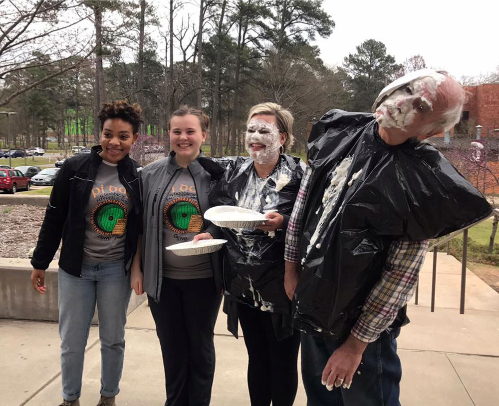 Amy Frets, EIT director of student services and retention, and Dr. Steven Minsker, professor of computer science, stand next to the students who hit them with a pie in the face to raise money for the Society of Women Engineers on Pi Day.