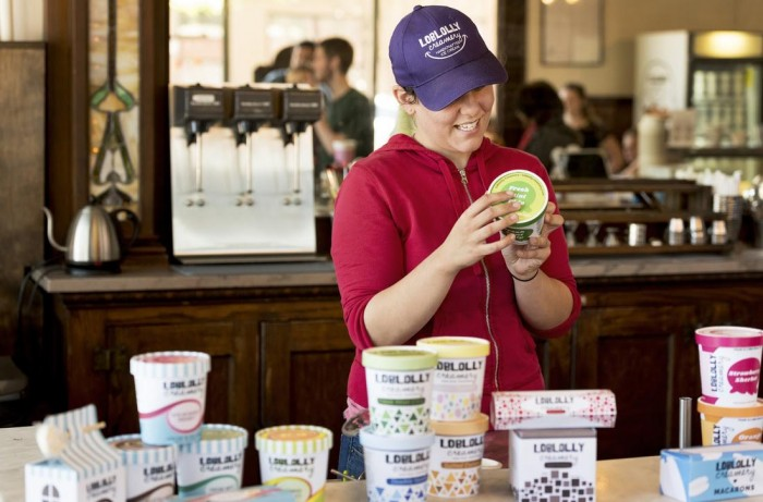 Sally Mengel, co-owner of Loblolly takes a look at the students projects during the final critique for the Package Design class as they present their Loblolly branding project (4 ice cream pint designs, a hot cocoa package, and a macaron package) at the Green Corner Store on May 1, 2017.