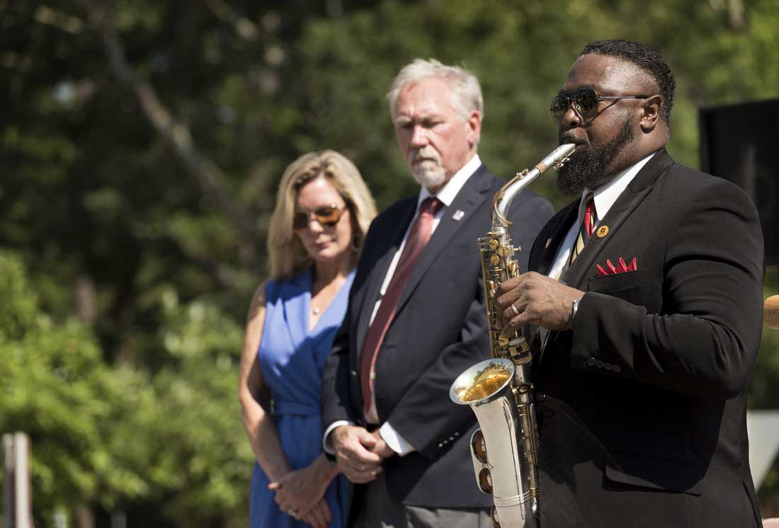 Janessa Rogerson and Chancellor Andrew Rogerson watch Michael Eubanks plays the taps during UA Little Rock's May 30 Memorial Day service. Photo by Lonnie Timmons III/UA Little Rock Communications.