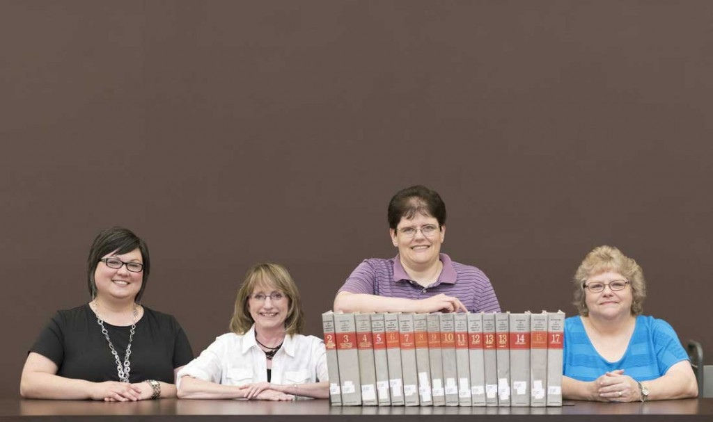 "Erin Fehr, Donna Rose, Karen Russ, and Carol Macheak hold volumes of ""The Handbook of North American Indians,"" the historic publication Ottenheimer Library has agreed to preserve."