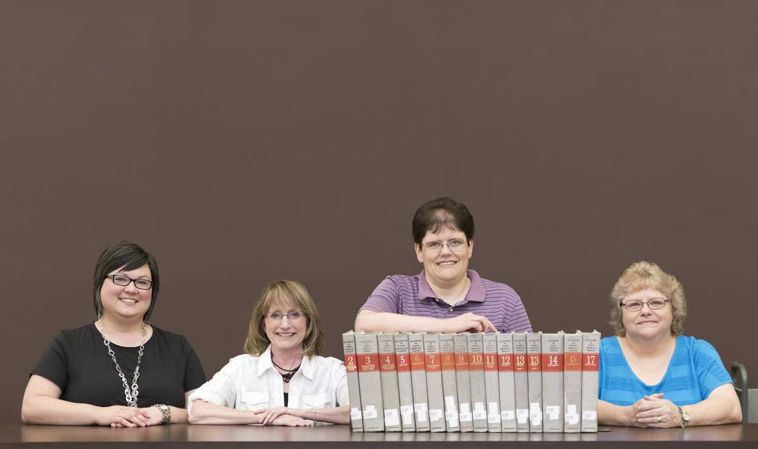 """Erin Fehr, Donna Rose, Karen Russ, and Carol Macheak hold volumes of """"The Handbook of North American Indians,"""" the historic publication Ottenheimer Library has agreed to preserve."""