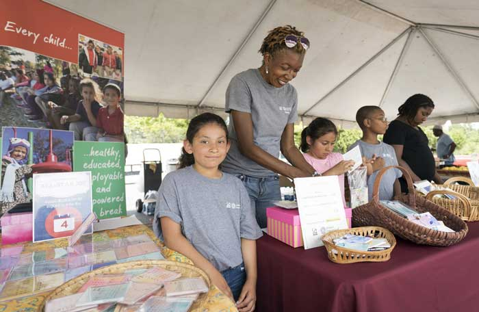 "University of Arkansas at Little Rock Children International students sell homemade products to raise money for the ""Victory Over Violence"" campaign at the University District Farmer's Market. Pictured, from left to right, include: second-grader Angela Salas, Camp Instructor Mary Virden, first-grader Aimar Salas, third-grader Mason Thomas, and fourth-grader Kirsten Ewings."
