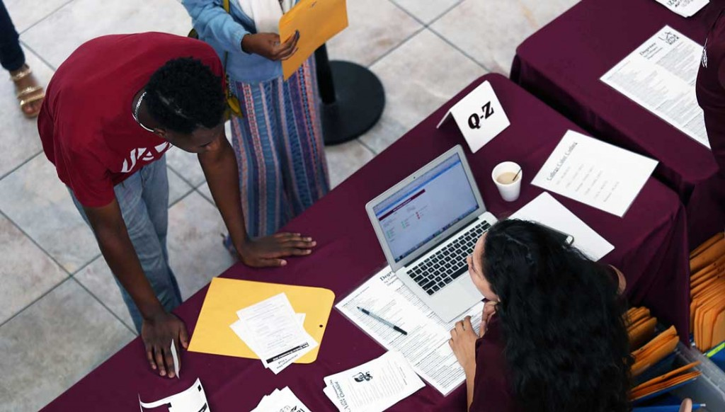 Admissions officials help a University of Arkansas at Little Rock student register for classes during a Fastlane event.