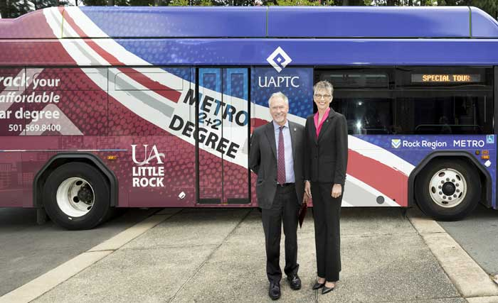 Chancellor Andrew Rogerson and UA-Pulaski Tech President Margaret Ellibee stand in front of a bus painted to celebrate a new partnership that allows UA Little Rock students to ride Rock Region METRO buses for free.