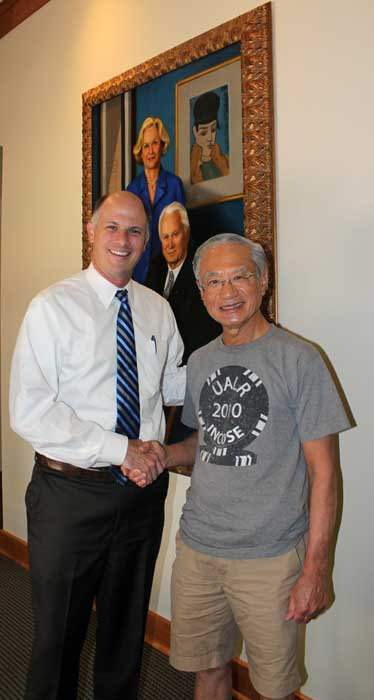 Christian O'Neal, vice chancellor for university advancement, shakes hands with Rising Star Workshop Director Yupo Chan in front of the portrait of the Baileys in the Bailey Alumni Center.