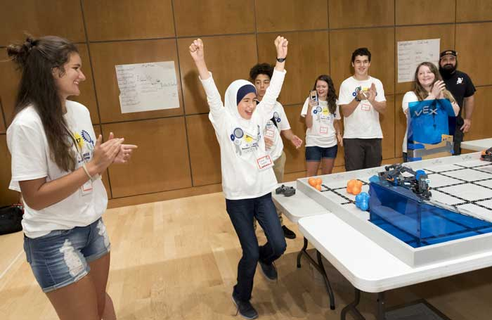"Neva Dagtas (middle) of Little Rock celebrates as her robot, ""Walle Jr.,"" wins the robotics camp competition for fifth and sixth graders. Photo by Lonnie Timmons III/UA Little Rock Communications."