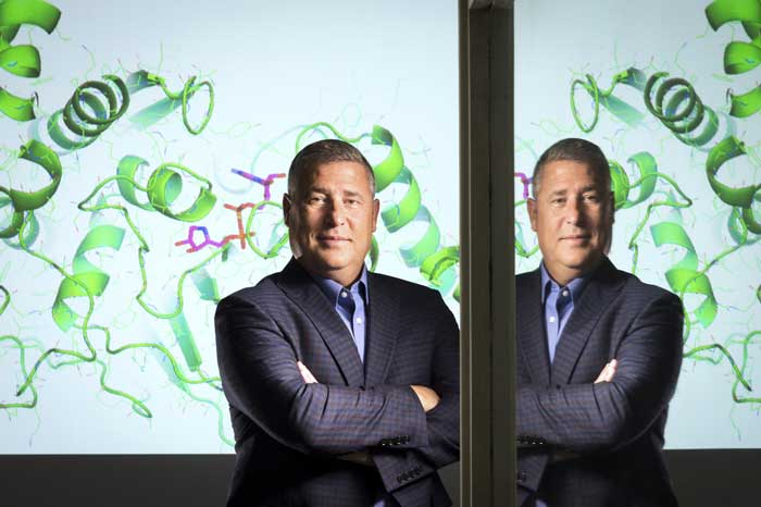 Dr. Darin Jones stands in front of a projected image of the crystal structure of the enzyme he is studying to develop an effective cancer treatment without the severe side effects of traditional therapies. Photo by Lonnie Timmons III/UA Little Rock Communications.