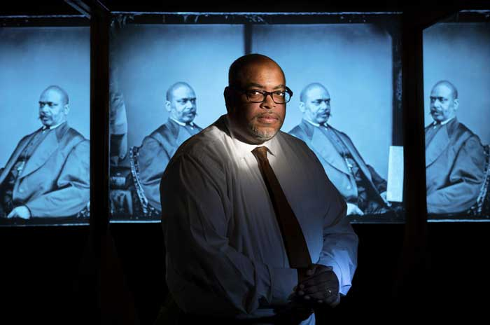 Brian Mitchell is photographed in front of a portrait of his ancestor, Oscar James Dunn. Photo by Lonnie Timmons III/UA Little Rock Communications.