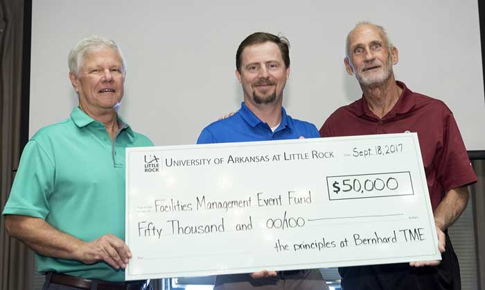Steven Ward (middle), chief operating officer of TME, presents a check to program co-founders Bob Adams, former vice chancellor for finance and administration, and Dave Millay, associate vice chancellor for facilities management. Photo by Lonnie Timmons III/UA Little Rock Communications.