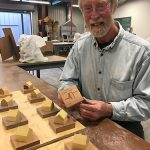 "Michael Warrick individually numbers the wooden ""spirit houses"" for CRE8."