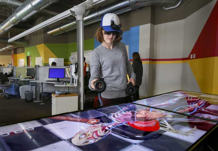UA Little Rock student Lea Poignant dissects a virtual life-sized cadaver using augmented reality and virtual reality equipment.