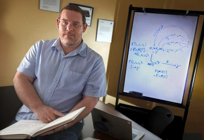 John Siratt works on algebraic equations in his office at UA Little Rock. Photo by Ben Krain.