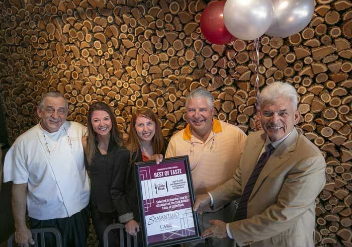 Taste of Little Rock honoree Alfred Williams, right, and staff members from the UA Little Rock Alumni Association Sarah Hamilton, center left, and Danielle Hendrix, center, present a Best of Taste Award to Samantha's Chef Marshall Smith, left, and owner Chris Tanner, center right. Photo by Ben Krain.