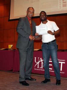Vernard Henley (left) presents Adewale Obadimu (right) with second place in the EIT Grad Award.