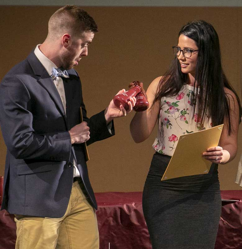 James Sellers and Rebecca Moreira admire chemistry beaker flasks they were awarded as recipients of the Department of Chemistry's Outstanding Graduating Seniors awards. Photo by Ben Krain.