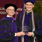 John DiPippa, interim dean of the Bowen School of Law, presents Cory Bates with the 2018 Student Public Service Award during the commencement ceremony on May 12.