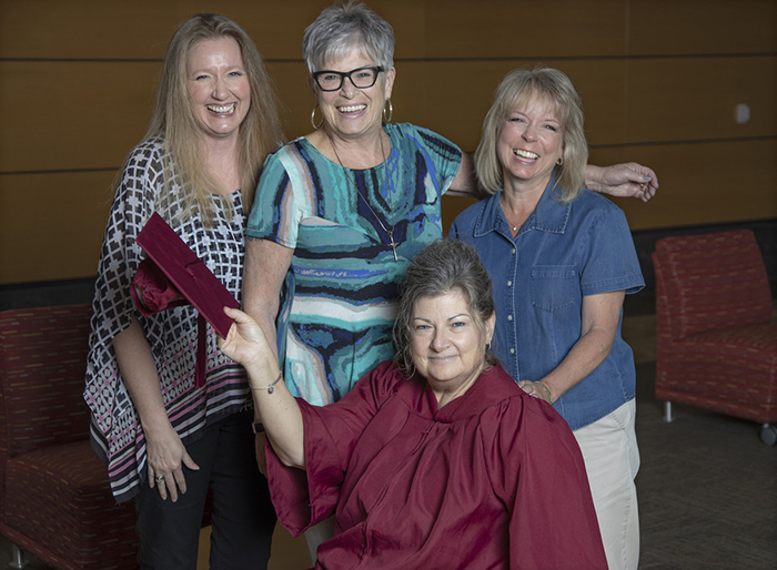 Tandie Kenser (seated) and her mother, Gennie Adair (center) visit Cindy Wallace (left) and Shannon Gwinn (right) in the UA Little Rock College of Business. Photo by Ben Krain.