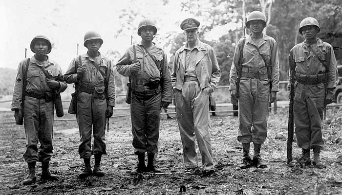 Gen. Douglas MacArthur, commander-in-chief of the Allied forces in the South Pacific, on an inspection trip of American battle fronts in late 1943. From left: Staff Sgt. Virgil Brown (Pima), 1st Sgt. Virgil F. Howell (Pawnee), Staff Sgt. Alvin J. Vilcan (Chitimacha), Gen. MacArthur, Sgt. Byron L. Tsingine (Diné [Navajo]), Sgt. Larry Dekin (Diné [Navajo]). Photo courtesy of U.S. Army Signal Corps.