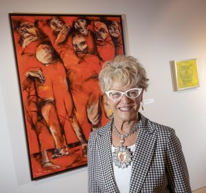"""Art collector Pierrette Van Cleve stands in front of the painting, """"My Surrounding People,"""" that she donated to UA Little Rock in Brad Cushman's honor. Photo by Ben Krain."""