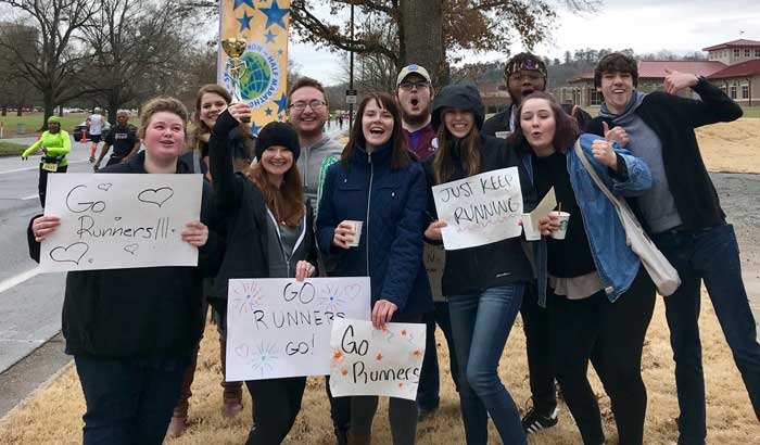 Members of the UA Little Rock Donaghey Scholars program cheer on runners who competed in the 2018 Little Rock Marathon.
