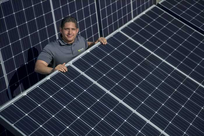 Victor Ruiz is shown with solar panels that he works with at his internship. Photo by Ben Krain.